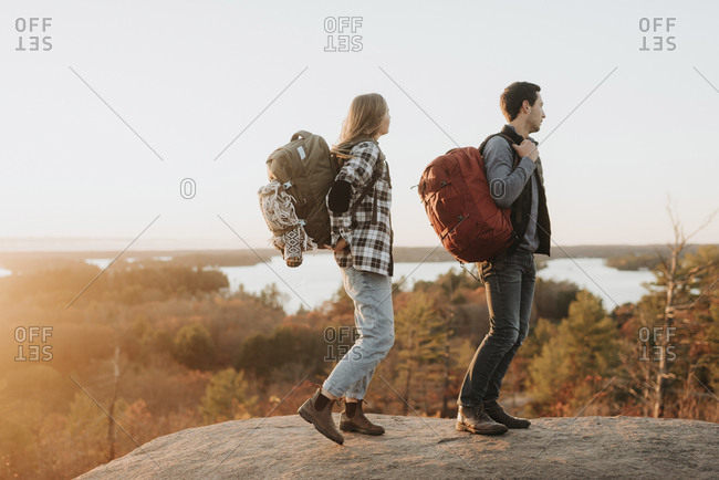 Young couple standing at edge of rocky outcrop admiring surrounding forest at autumn sunset