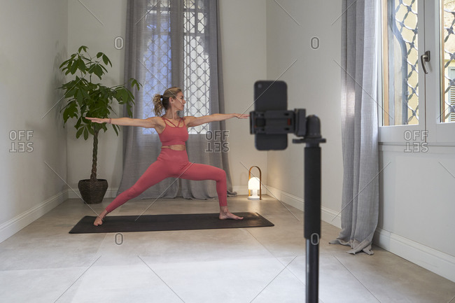 Female yoga instructor filming herself on mobile phone for online lessons in exercise room