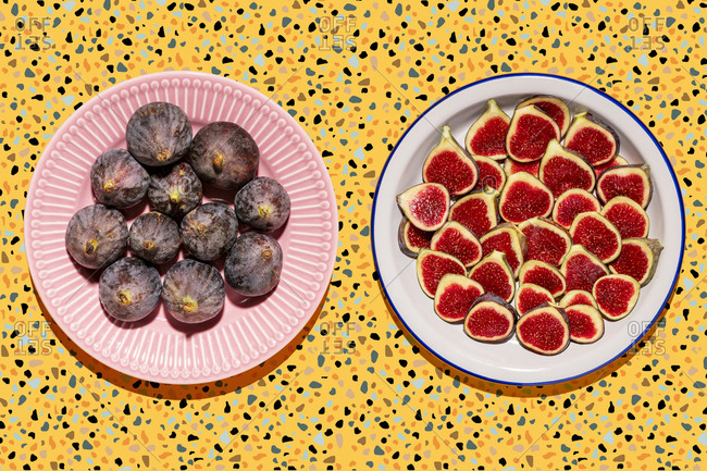 Studio shot of two plates with halved and whole figs against yellow terrazzo background