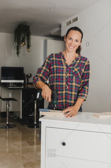 Smiling woman using electric drill on wood material while standing by cabinet at home