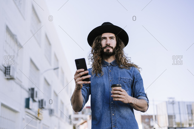 Stylish man with disposable coffee cup looking away while holding smart phone in city