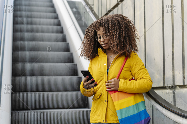 Woman with multi colored purse using mobile phone while standing on escalator in city