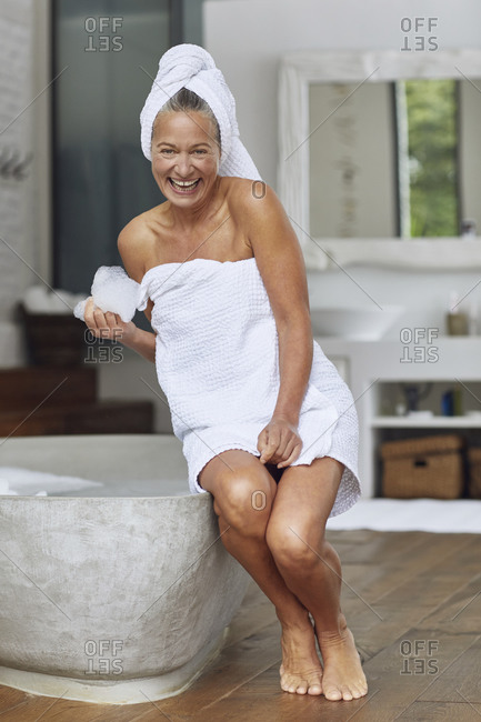 Happy mature woman playing with bubbles while sitting at edge of bathtub in bathroom