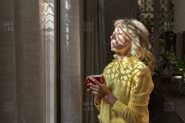 Sunlight falling on woman holding tea cup while standing with eyes closed in kitchen