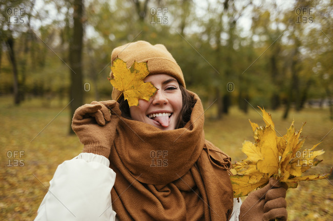 Happy woman covering eye with autumn leaf while sticking out tongue in public park