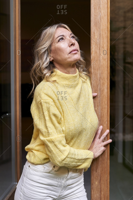 Thoughtful mature woman in yellow sweater looking up while leaning on door at home