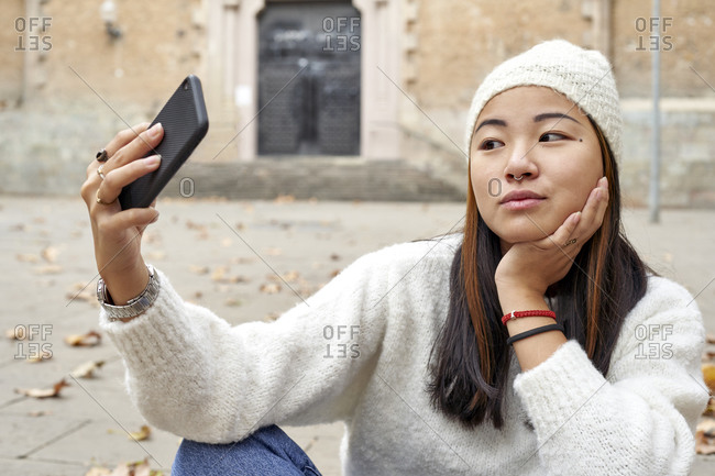 Young woman with hand on chin listening to video call while sitting on footpath