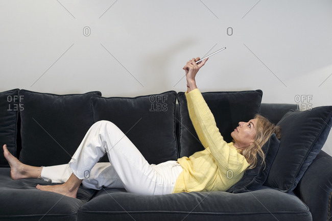 Mature woman with hands raised using digital tablet while lying on sofa at home