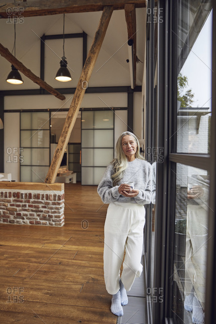 Mature woman with coffee cup day dreaming while leaning on glass door at home