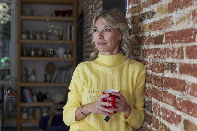 Mature woman with tea cup looking away while leaning on brick wall in kitchen