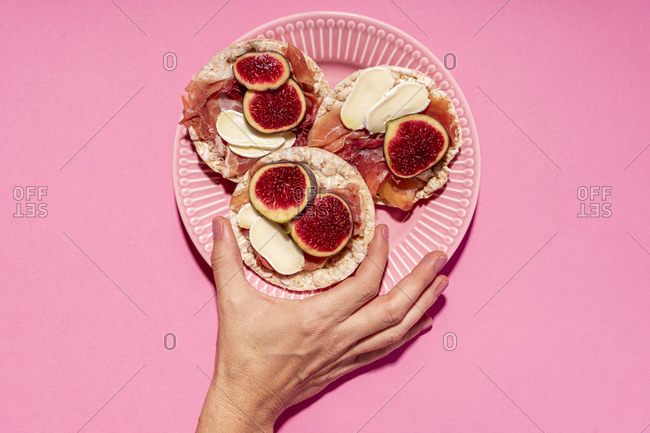 Hand of woman picking up rice cake with serrano ham- cheese and fig slices