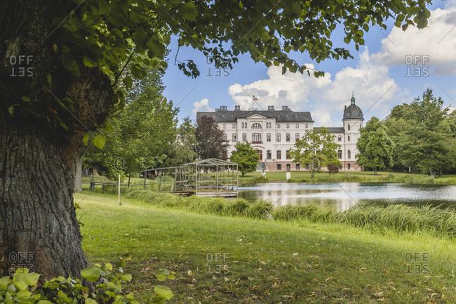 Germany- Schleswig-Holstein- Fargau-Pratjau- Salzau stream flowing through public park with Gut Salzau mansion in background