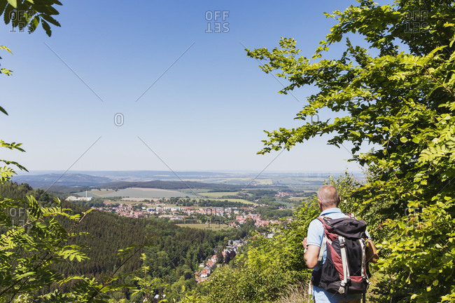 Germany- Thuringia- Bad Tabarz- Senior hiker admiring view of town in Thuringian Forest during spring