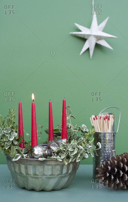 Studio shot of DIY Advent decorations including candles- twigs- pine cone- matches and baking pan