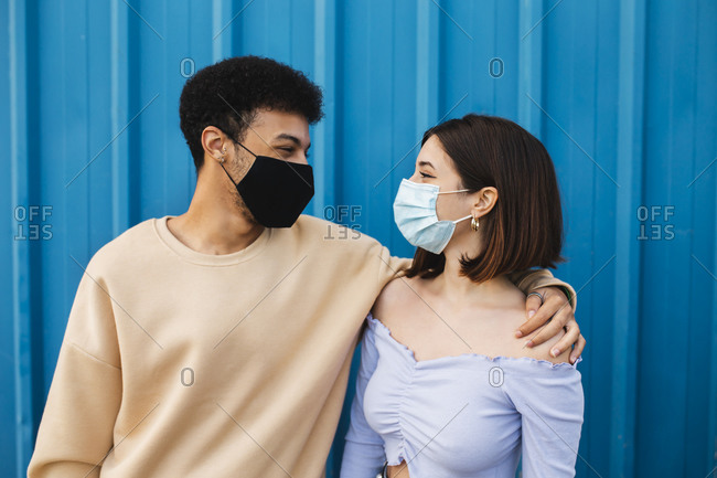 Young couple wearing protective face mask looking at each other while standing against blue wall