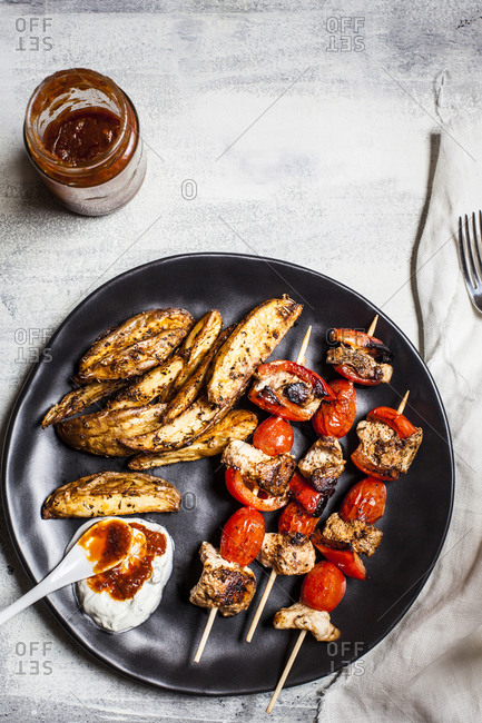 Gyros chicken skewers with tomatoes- bell peppers- potato wedges in plate by tzatziki on table