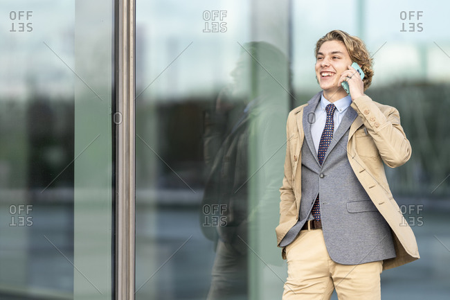 Happy businessman with hand in pocket talking on mobile phone while standing by glass wall