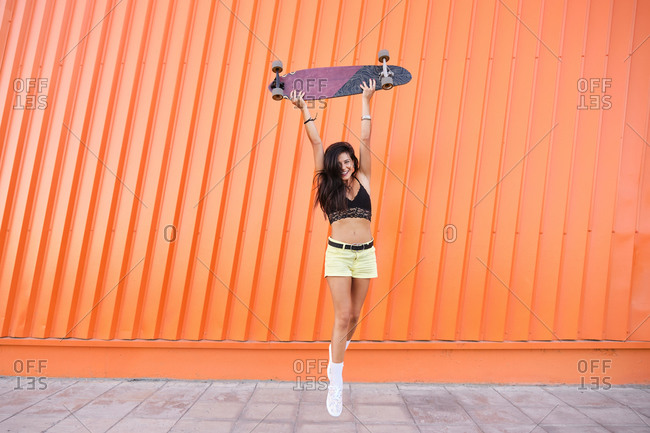 Portrait of young woman standing in front of corrugated iron wall with longboard in hands