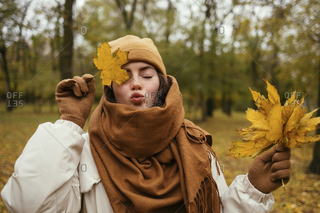 Young woman with eyes closed puckering while covering eye with autumn leaf in public park