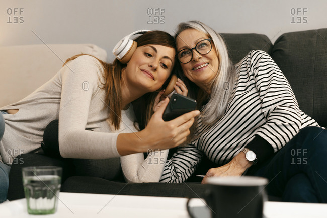 Woman with headphones showing mobile phone to senior woman while resting on sofa at home