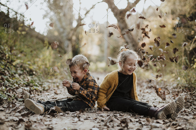 Cheerful girl and boy playing with dry fallen leaf while sitting on footpath in forest