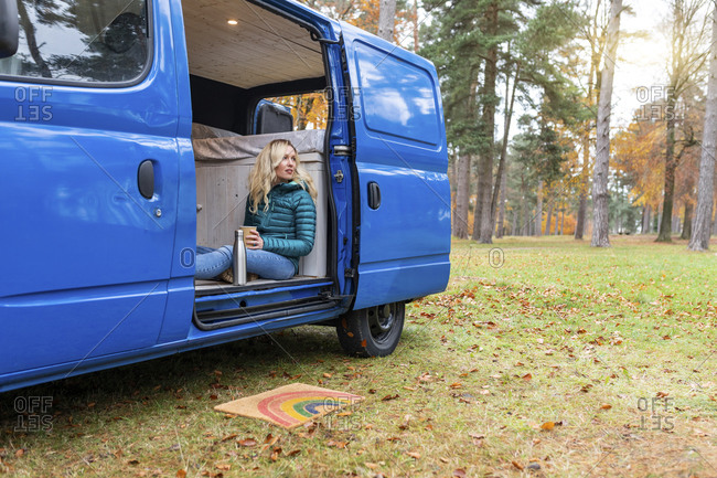 Thoughtful woman holding tea cup while sitting at door of camper van in Cannock Chase