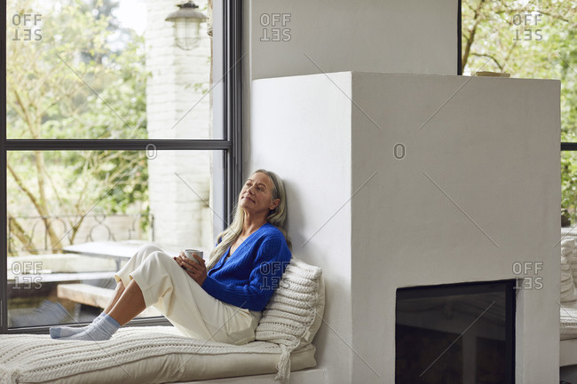 Mature woman with coffee cup day dreaming while leaning on wall of fireplace at home