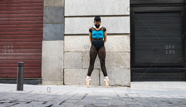 Ballet dancer wearing protective face mask standing tiptoe with hands behind head on footpath during COVID-19
