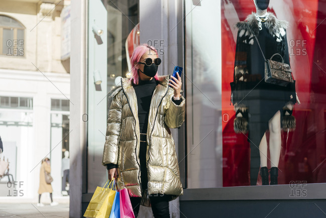Fashionable woman with face mask carrying shopping bags while using mobile phone standing by store window