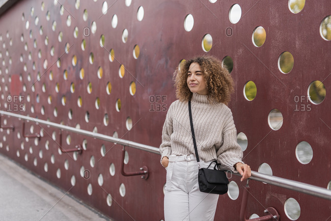 Beautiful young blond woman standing with hand in pocket while leaning on railing against metallic wall