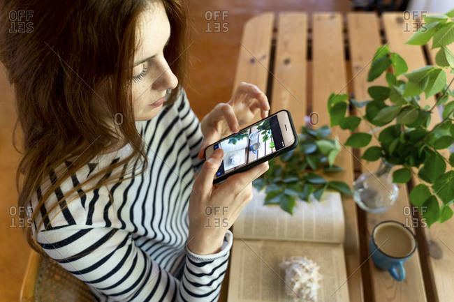 Young woman photographing coffee cup and book on table through mobile phone while sitting at home