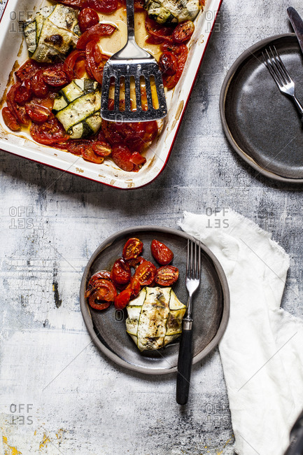 Grilled tomato with spinach and feta cheese stuffed zucchini ravioli in plate with fork on table