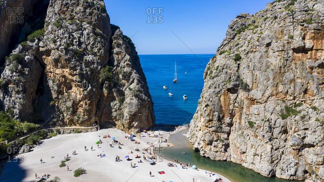 Drone shot of Mallorca beach in between rock mountains-Torrent De Pareis- Sierra De Tramuntana- Balearic Islands- Spain