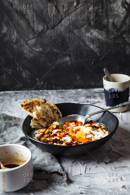 Breakfast of yogurt and spicy paprika butter on poached eggs in bowl by coffee cup on table