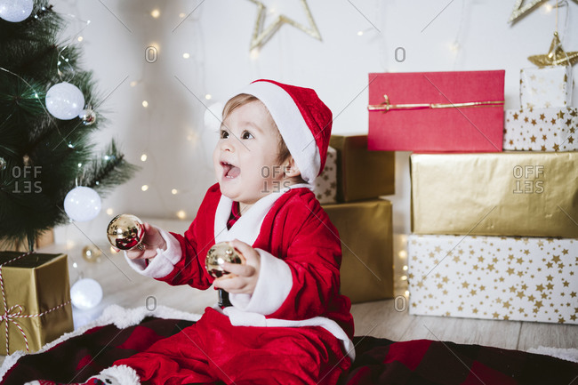 Playful baby boy in Santa Claus costume playing with bauble while sitting on blanket at home during Christmas