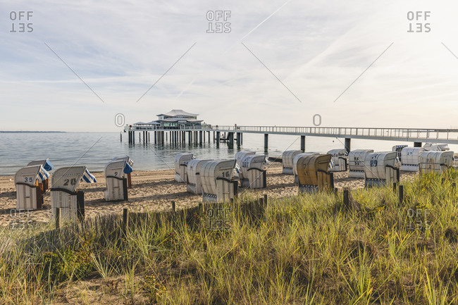 Germany- Schleswig-Holstein- Timmendorfer Strand- Hooded beach chairs on sandy coastal beach with teahouse at end of pier in background