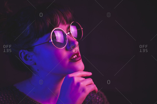 Tranquil female in stylish round glasses standing on dark background in pink and blue neon illumination