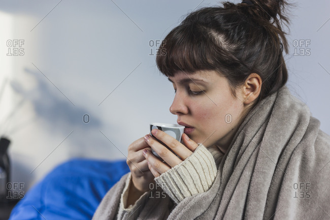 Side view of female in domestic sweater wrapped in warm plaid drinking hot espresso at home in cold winter season