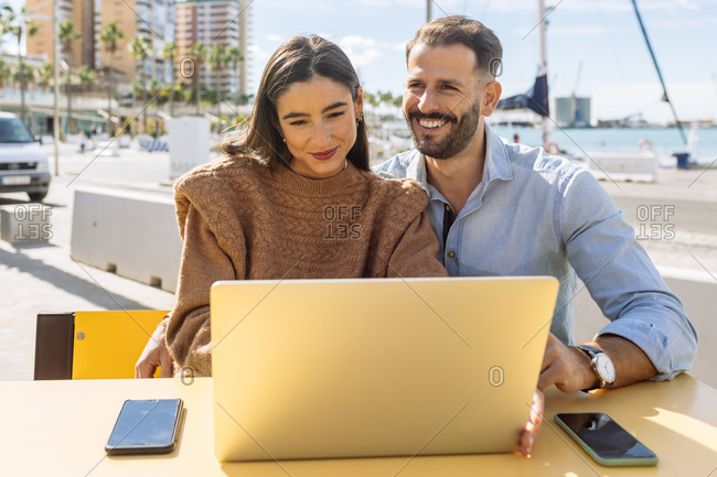 Side view of happy young ethnic smiling and pointing at laptop screen while watching funny video with excited stylish girlfriend on cafe terrace on sunny day