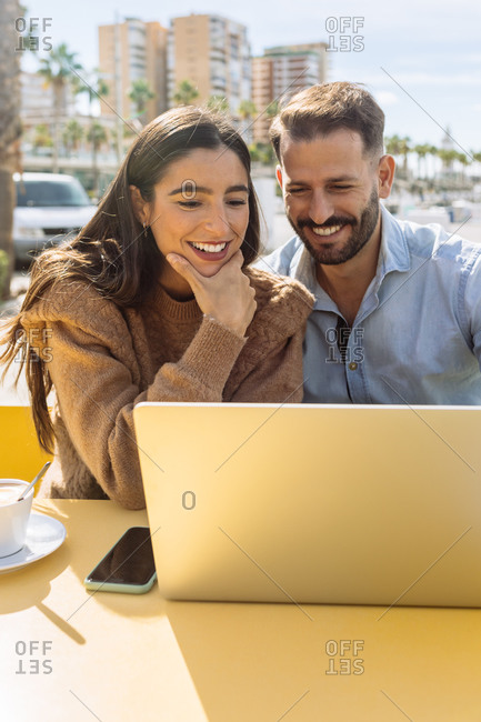 Romantic young ethnic guy in classic outfit hugging and kissing cheek of stylish girlfriend working distantly on laptop in street cafe near sea