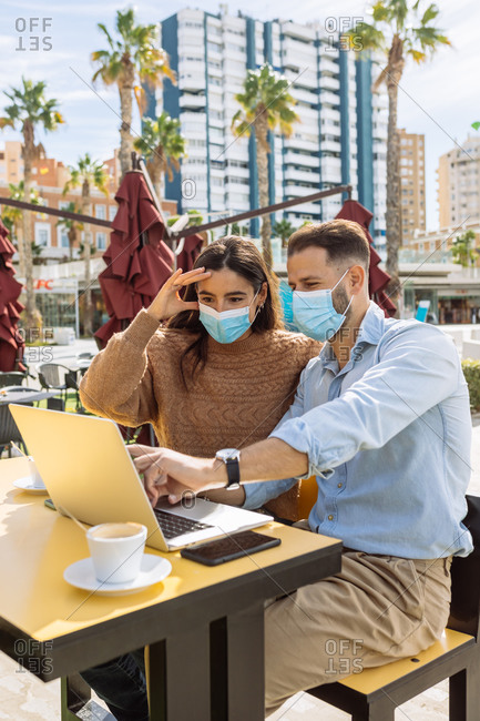 Unrecognizable young ethnic female entrepreneur in stylish clothes and medical mask talking on smartphone and looking at boyfriend working on laptop in street cafe during coronavirus