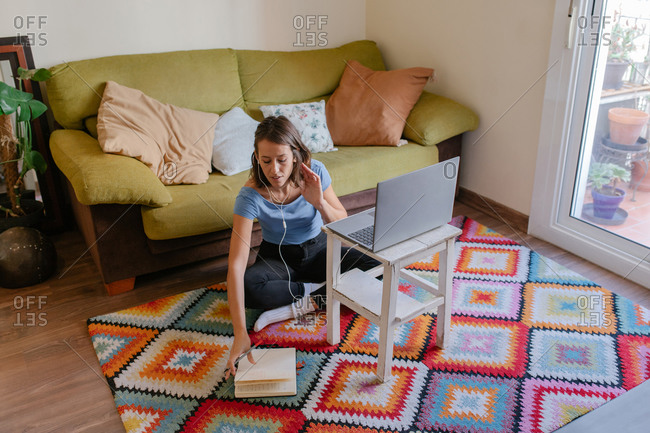 Focused adult female remote employee sitting on floor in front of laptop and taking notes in planner while working online at home