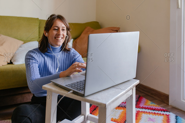 Adult female remote specialist in casual outfit discussing business issues during video conference via laptop while working in living room at home
