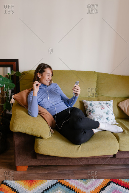 Businesswoman sitting in leisure on sofa and browsing mobile phone in office