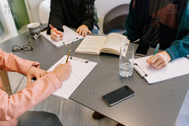 From above of crop unrecognizable couple writing on papers while solving psychological test during therapy with female doctor