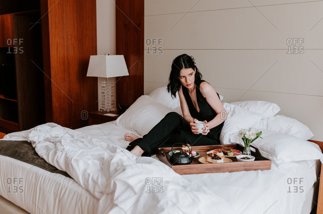 Calm female in elegant black dress relaxing on bed and enjoying assorted tasty food served on wooden tray in luxury hotel