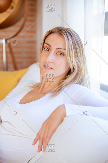 Young confident female with blond hair in white blouse resting on comfortable sofa and looking at camera