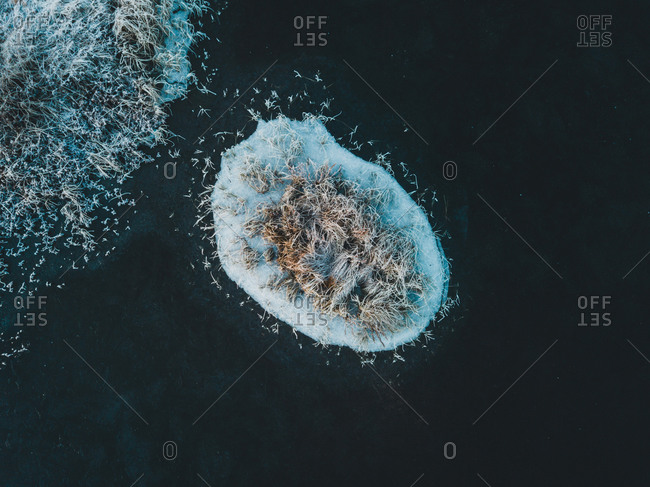 Spectacular drone view of small island covered with snow in sea in winter