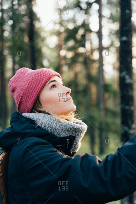 Side view of tranquil female traveler in warm clothes standing in coniferous woods in morning and enjoying nature in winter