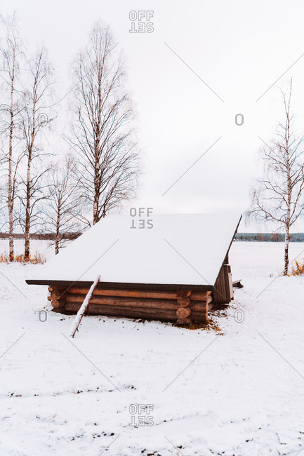 Small wooden shack in field covered with snow under gray sky in winter